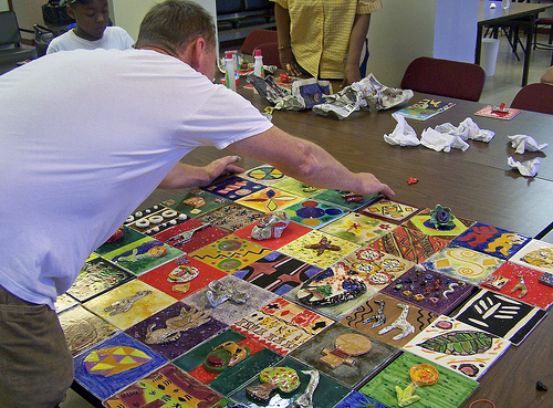 Patrick works on the layout of art tiles for the mural installation.