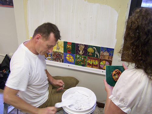 Curator Patrick Dennis and Teaching Artist Jennifer Wade install the tile mural at Langston Hughes Senior Center.